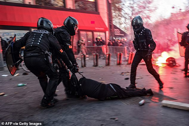 Police drag man on the ground during a demonstration against the 'global security' bill in Paris on Saturday