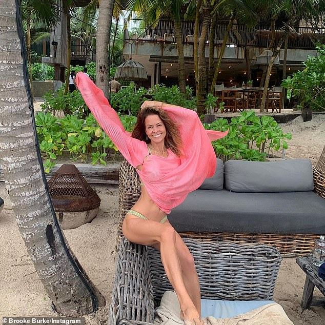 Classic: Brooke rocked a neon green bikini with a light pink shawl as she sprawled out on the beach with her beau