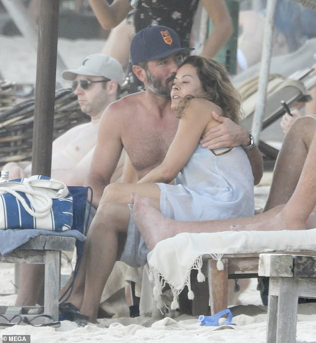 Love: Scott wrapped his arm around his loving wife for a quick moment of calm as they relaxed amid a group of friends