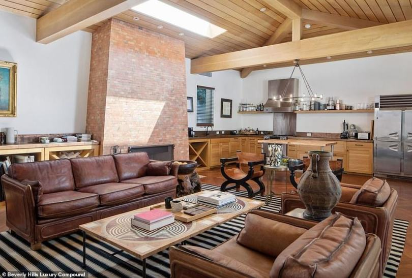 Another area: This room has a small kitchen and a brick fireplace with a living room space as well as beamed ceilings