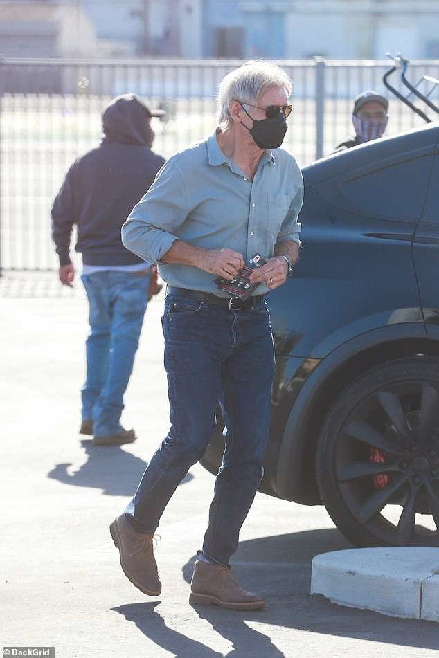 Rock solid: The legendary actor and pilot looked leading man fit in jeans, button-down shirt and suede boots