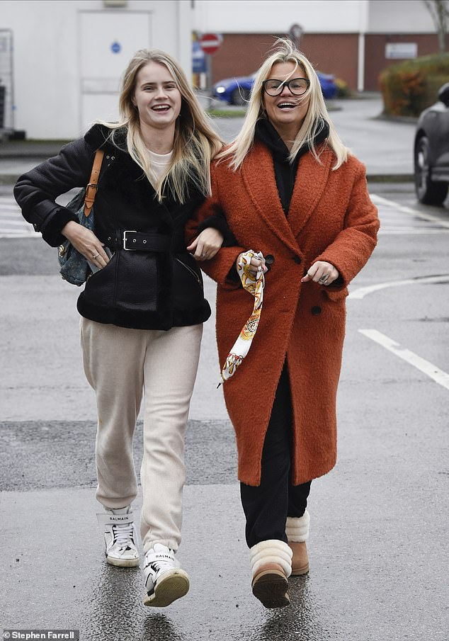Casual: The former Atomic Kitten star layered her look with an orange overcoat, while also sporting a pair of black thickly-rimmed glasses