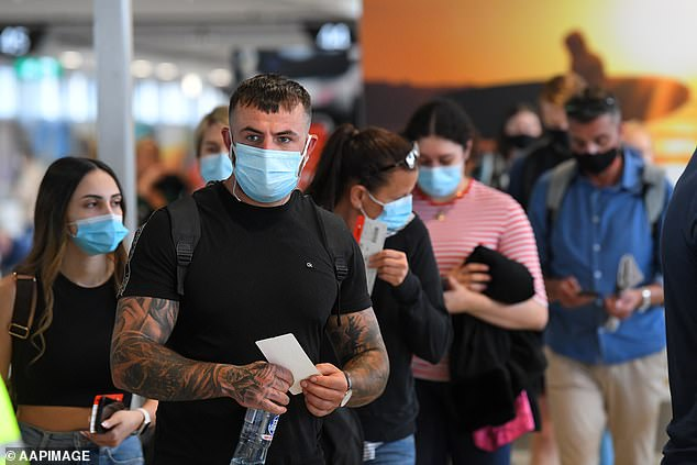 Anyone in the Minto area who have coronavirus symptoms are being asked to get tested (pictured, travellers arriving into Sydney on November 23)