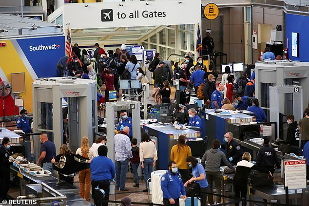 The CDC has warned Americans to postpone their travels plans and stay at home for Christmas and the holiday season. Pictured: Travelers go through security before boarding flights at Denver International Airport in Colorado, November 24