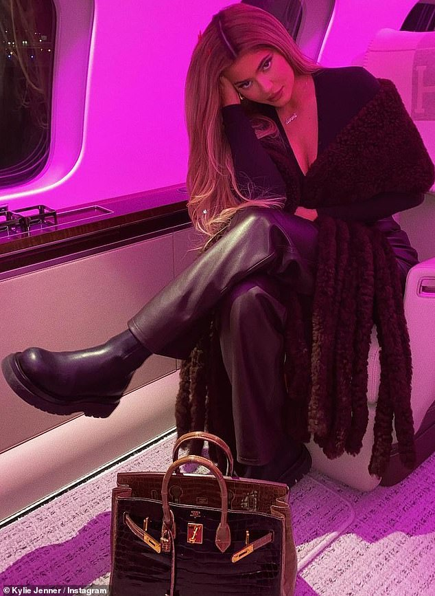 Sleek and chic:Kylie shot her best smoldering supermodel stare at the camera while lounging in a plush-looking airline seat with purple back-lighting