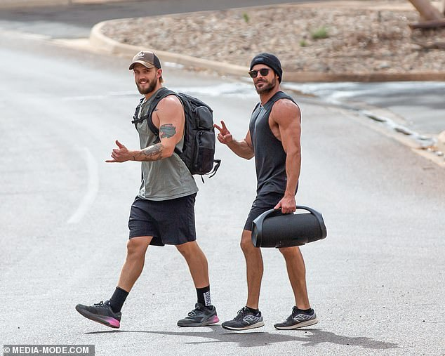 Quite the pair: Zac appeared in high spirits as he headed back to his hotel with his personal trainer, who greeted photographers with a shaka as he walked beside the acting hunk