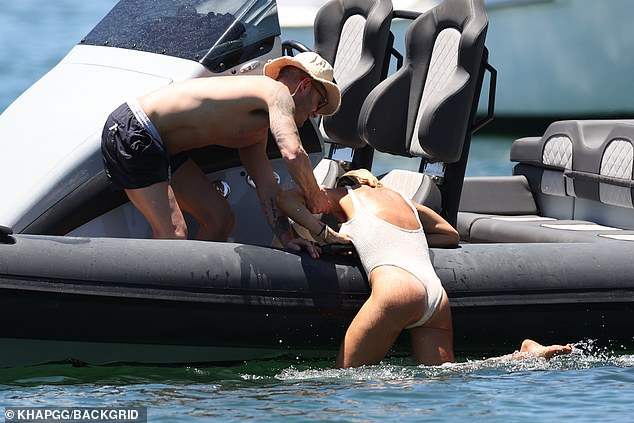 Man overboard! Michael Clarke struggled to pull his swimsuit-clad girlfriend Pip Edwards onto their inflatable boat during a boozy day on Sydney Harbour on Sunday