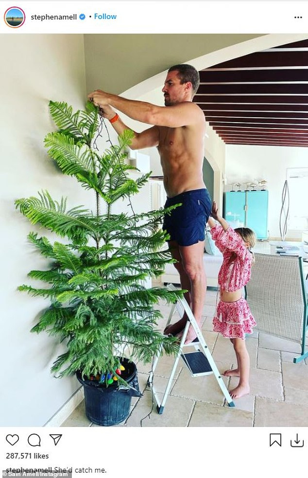Sweet snap: Stephen Amell showed off his toned physique while hanging lights on a tree as his daughter Mavi adorably tried to hold him up on a step ladder