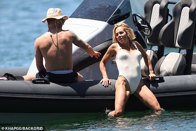 Slippery situation:At first, the sportsman tried to heave his ladylove upwards by pulling her arm, but it quickly became apparent that Michael would have to haul her legs onto the boat as well
