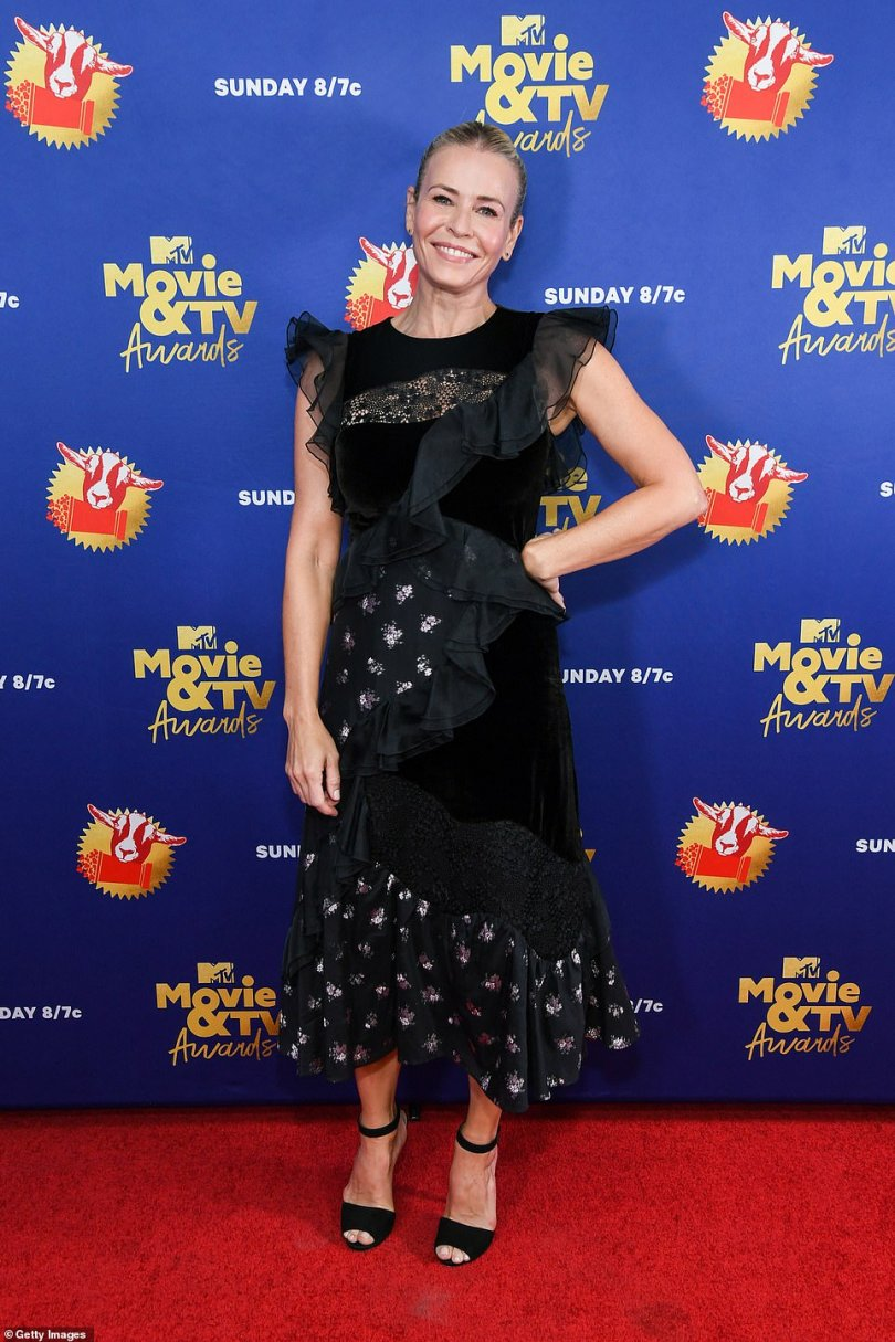 Flower power:Chelsea Handler looked simply ageless in a black, ruffled chiffon dress that featured hunts of floral fabric throughout