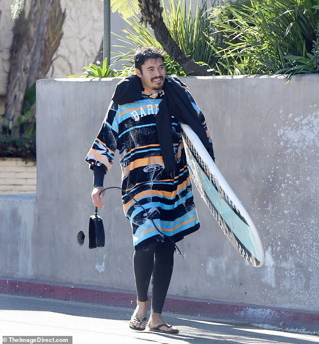 Later on: Henry was seen making his way on the sidewalk, draped in a colorful striped poncho as he held his surfboard and walked along in black flip-flops