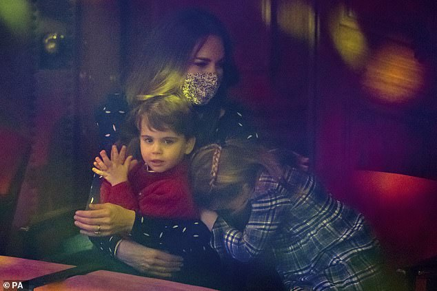 The Duchess of Cambridge with Prince Louis on her lap as Princess Charlotte rests her head of her mother ahead of the performance