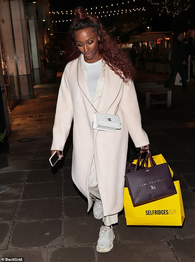 Festive: She appeared to have a successful Christmas shopping trip as she was seen laden with two yellow carrier bags from Selfridges as she strutted down the street