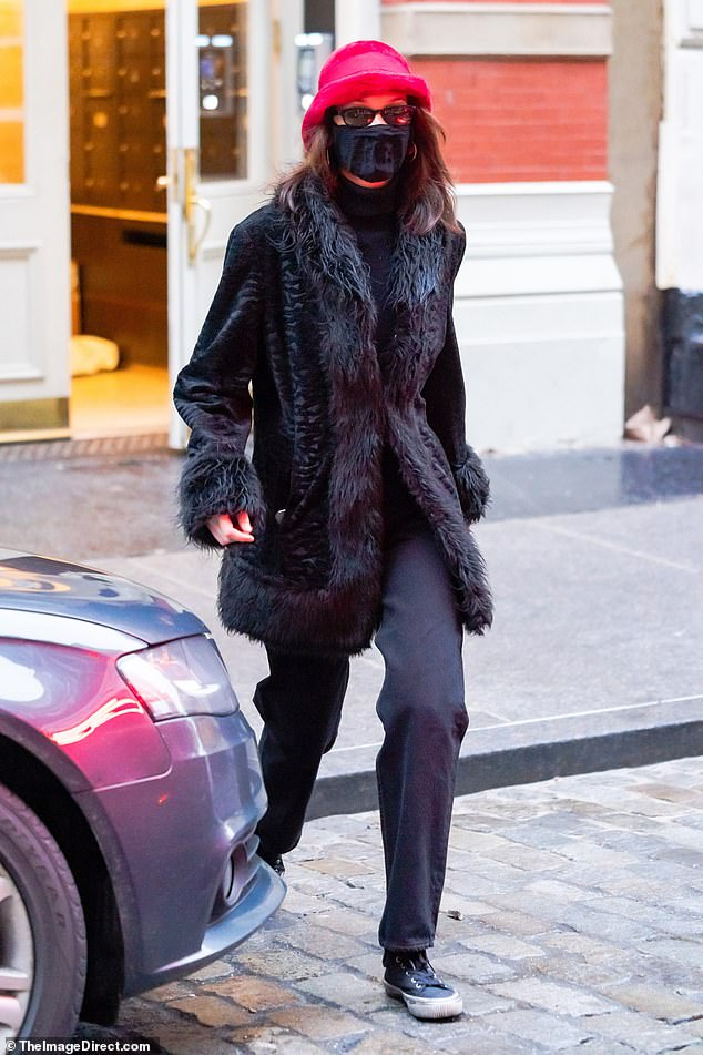 Trendsette: Bella Hadid was seen in Manhattan on Saturday afternoon rocking a chic winter look consisting of a bright pink hat and fur-trimmed coat