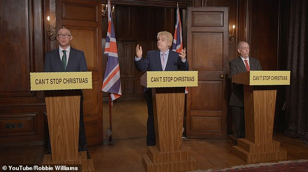 That's a bit different!The singer sported Boris' famous blonde hair as he spoke to the nation from the podium, with the government's usual Stay Alert slogan replaced with Save Christmas