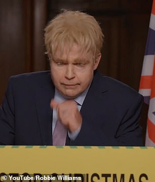 A striking resemblance! In the video Robbie dons a blonde wig and suit to mimic Boris