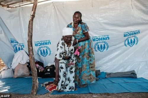 Ethiopian Asafu Alamaya (L), an 80-year-old blind woman who fled the Tigray conflict, is helped by her daughter at the Um Raquba refugee camp in Sudan's eastern Gedaref state, on December 12, 2020: the UN expressed frustration at lack of access to Tigray