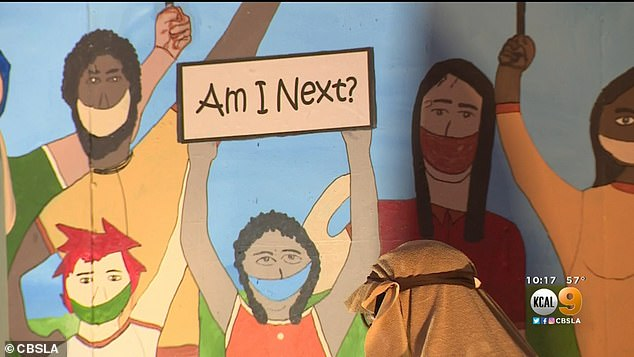 The scene shows Mary with her arms in the air mirroring demonstrators, Jesus in his crib while Joseph tends to him in front of a mural of BLM protesters