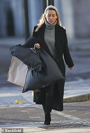 On the go: She completed her look with a pair of black heeled boots