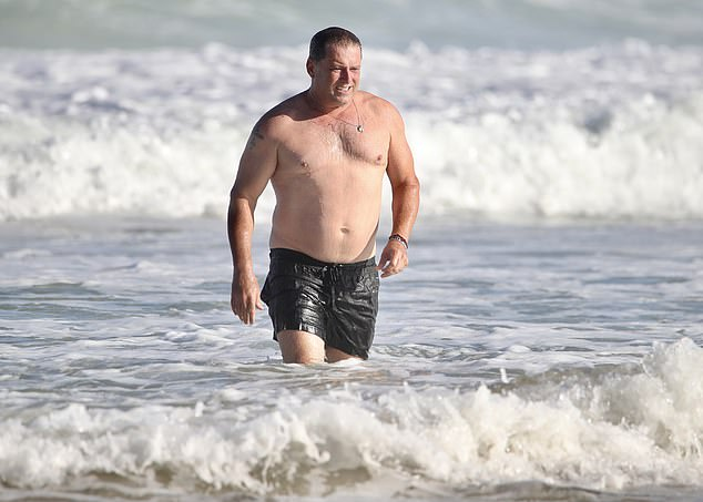 Wading in: Wearing just a pair of black boardshorts, Karl ran through the surf after immersing himself fully under the water