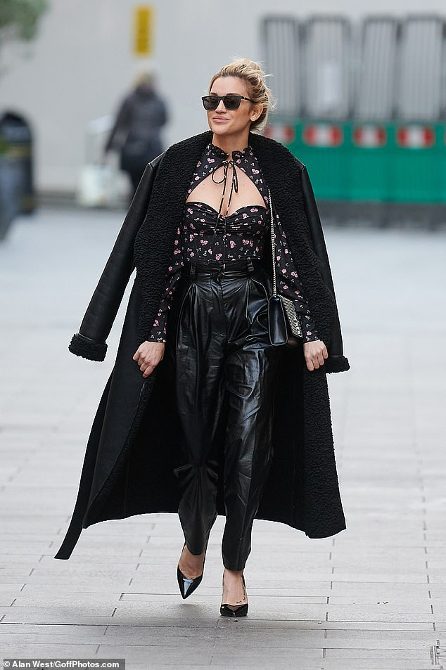 Showstopping:The Pussycat Dolls star, 39, turned heads in a black floral cut-out top and black leather-look trousers as she strutted down the street