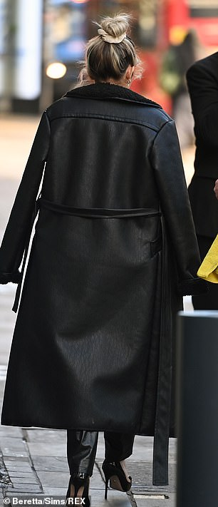 Snug: The star kept warm in the cool December weather as she donned a long black belted coat