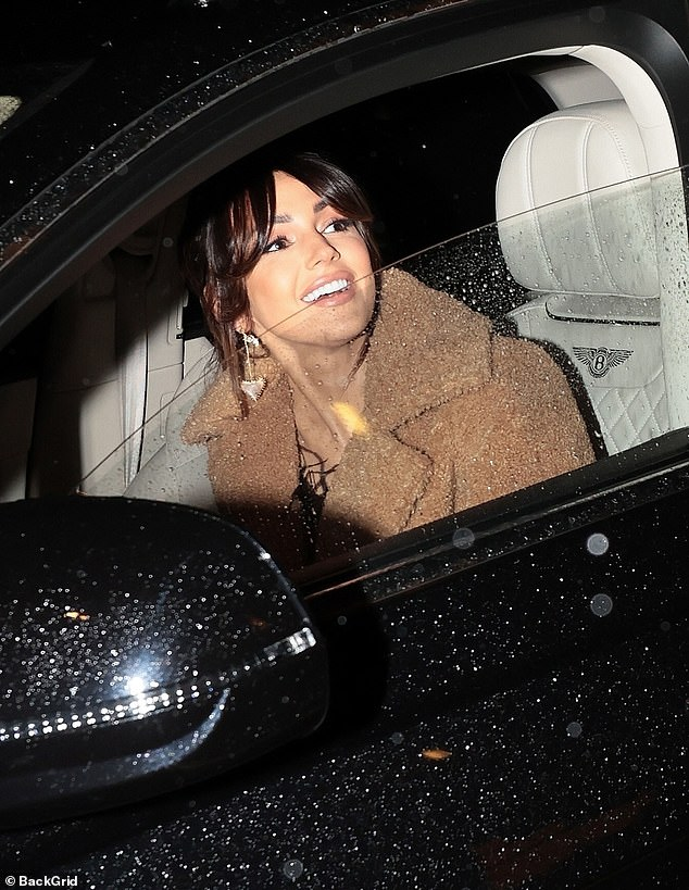 Sitting pretty: The Corrie star flashed a look at her heart earrings as she waited for Mark in the car, sheltering from the rain