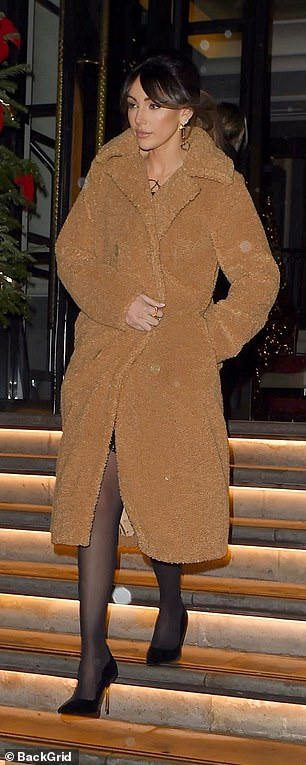 Gorgeous: Michelle, 33, showed off a hint of her legs in a mini dress layered under a cosy teddy coat for her exit from the hotel