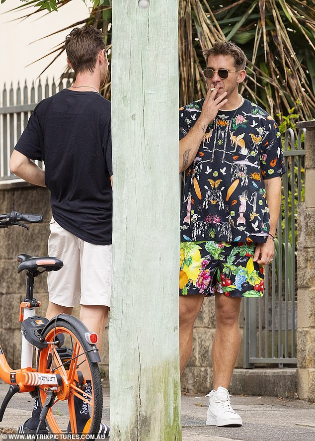 Clashing: The star was wearing a colourful shirt with his printed boardshorts