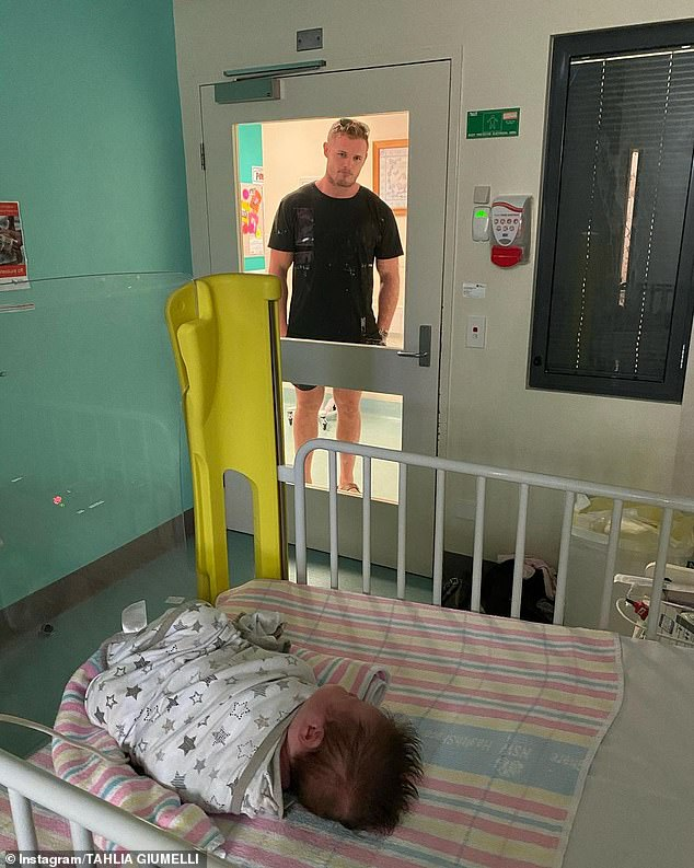 Sad: NRL player Tom Burgess is facing the heartbreaking prospect of being unable to see his baby daughter in hospital until she receives the results of her Covid-19 test. Tom's fiancée, Tahlia Giumelli, revealed her family's heartache on Instagram on Thursday, sharing this photo of the rugby league star peering at his daughter through the hospital room's glass windows