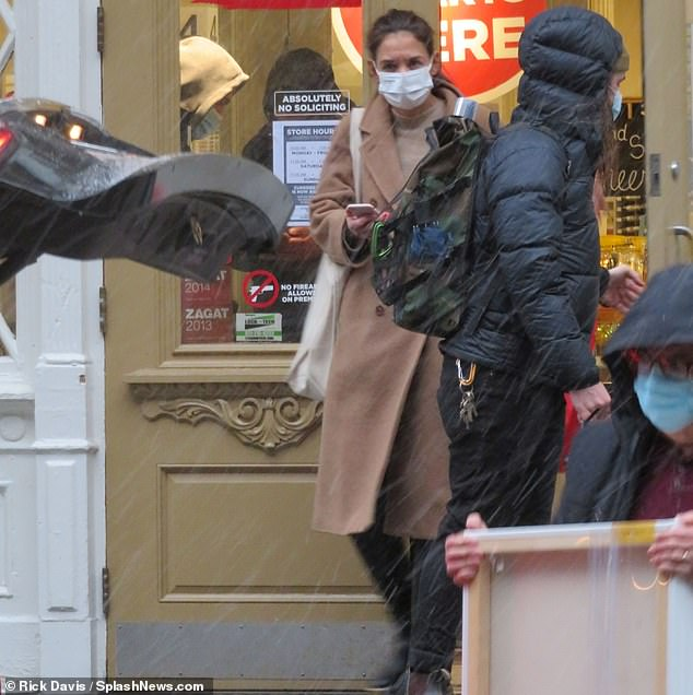 Katie Holmes bundles up for Christmas shopping at an art store amid New York City's snowy weather