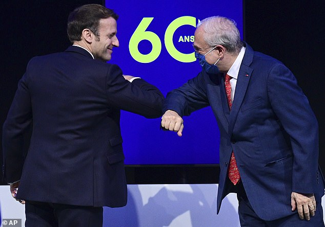 MONDAY: Macron, without a mask, bumps elbows with theOECD's 70-year-old Secretary General Angel Gurria on Monday