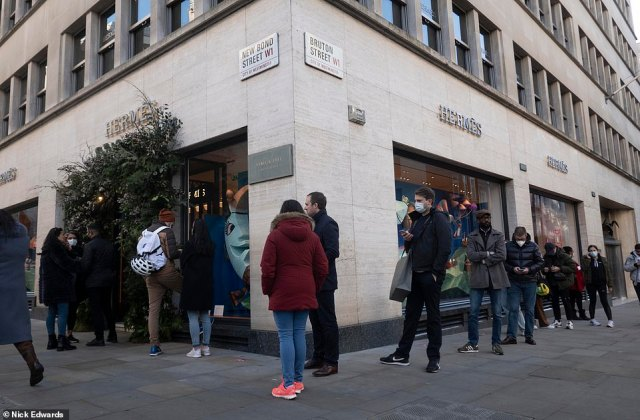 Pictures taken on Bond Street today showed thousands of shoppers rushing to make their final Christmas purchases - including dozens waiting patiently outside luxury designer Hermes (pictured)