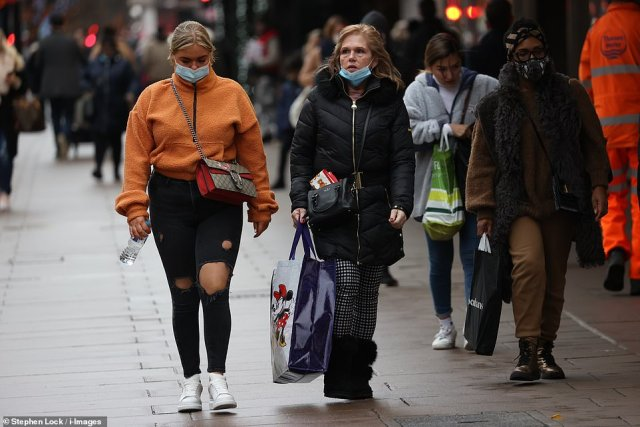 Masked shoppers braved the rain and Covid-19 warnings on the first of four big Christmas shopping days in the UK