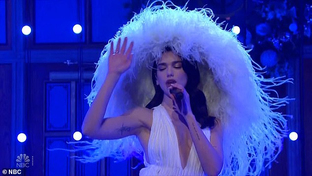 Angel in white: She returned to the stage to perform her track Levitating, as she wore a ridiculously wide-brimmed white feather hat with a matching plunging dress, featuring a long train that blew around her in the wind