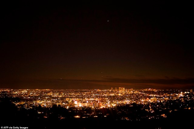 Planets Jupiter and Saturn (centre, top) are seen above the Los Angeles skyline during the great conjunction as seen from the Griffith Observatory, December 21, 2020