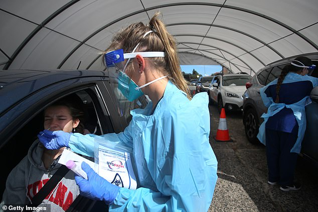 Scamwatch has received over 5170 scam reports mentioning coronavirus, with almost $6.3million in reported losses since the outbreak began. Pictured: a nurse conducts a swab at Bondi's test clinic on November 4