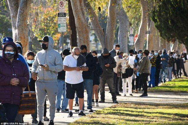 People wait in a long line for a free COVID-19 test at a pop-up site in Van Nuys, Calif. Los Angeles County on Tuesday