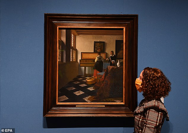 """A gallery employee poses for photographers next to a painting entitled """"At Lady at the Virginals with a Gentleman (The Music Lesson)"""" by Dutch master Johannes Vermeer"""