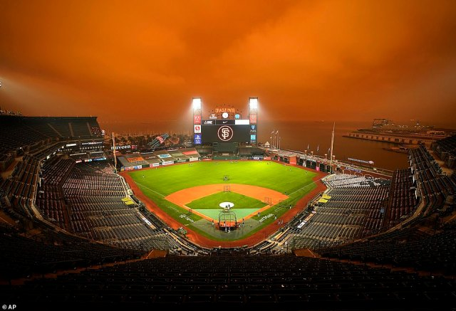 Smoke from wildfires obscures the sky over Oracle Park in San Francisco as the Seattle Mariners take batting practice before their baseball game against the San Francisco Giants on September 9