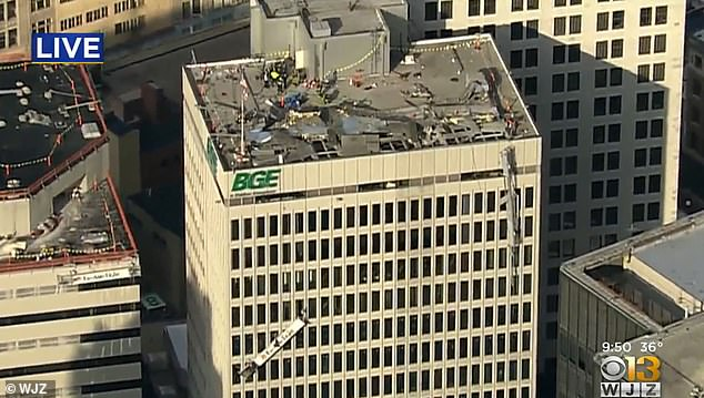 An aerial view of the building shows damage on top of the roof