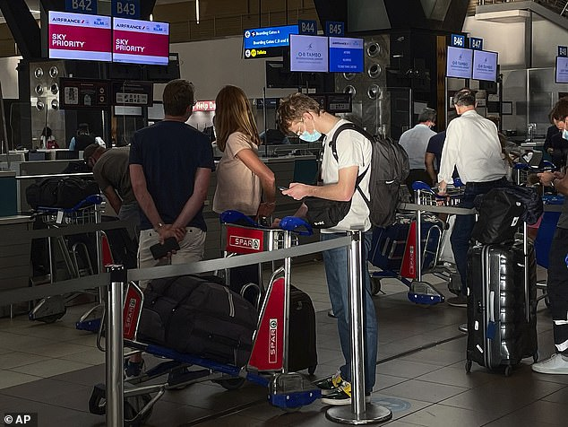 Passengers wait in line at a Johannesburg airport on Monday as South Africa, like Britain, finds itself isolated by coronavirus-related travel bans