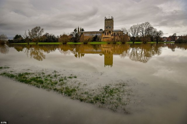 Floodwater surrounds Tewkesbury Abbey in Gloucestershire yesterday as hundreds of alerts and warnings were put in place