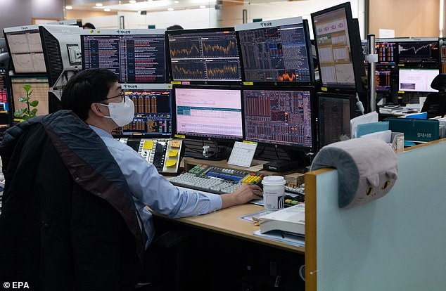 A dealer works in front of monitors at the Hana Bank in Seoul, South Korea, on Christmas Eve