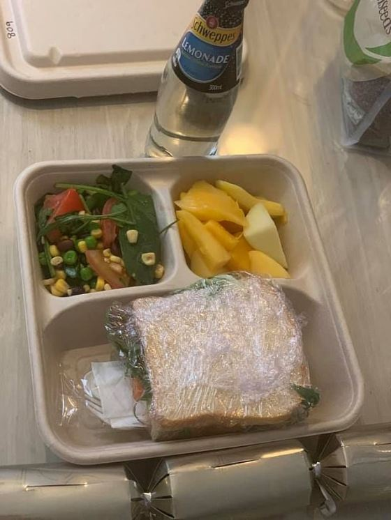 One person in quarantine posted a photo of a salad sandwich wrapped in cling film, served on a cardboard plate along with a vegetable salad and fruit.  She also seems to have gotten Schweppes lemonade and a Christmas cracker to celebrate the occasion