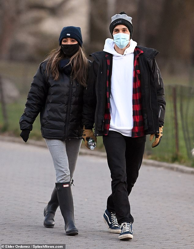 Bachelorette Tayshia Adams holds hands with fiance Zac Clark as they enjoy a romantic stroll