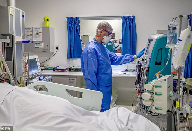 The data, which was recorded up until December 23, stated 1,911 people had died in hospitals in England after testing positive for Covid-19. Pictured: Health worker on the intensive care unit (ICU) at Whiston Hospital in Merseyside