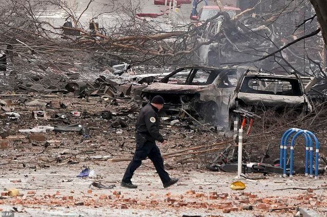 A law enforcement member walks past damage from an explosion in downtown Nashville