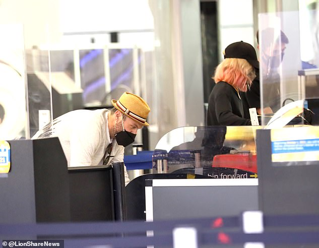 Catching a flight: Despite the majority of her face hidden behind a face mask, she was immediately recognizable by her platinum blonde hair with pastel pink ends