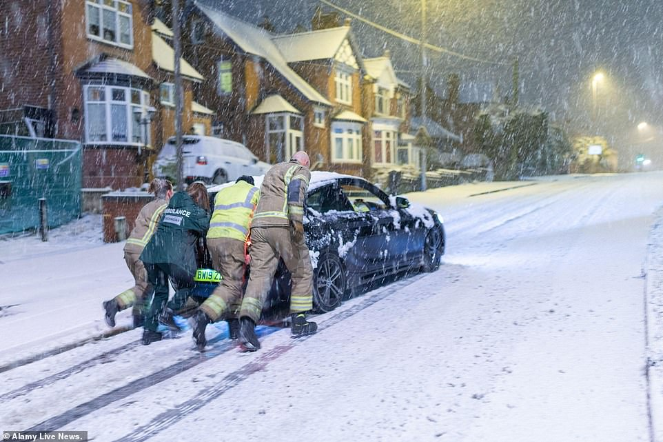 A fire crew pushes a stranded paramedic's car up a snowy hill in the West Midlands this morning, as she tries to make it into work for her day's shift